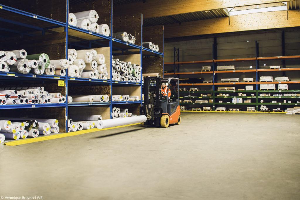 élévateur transportant un rouleau dans un entrepôt logistique