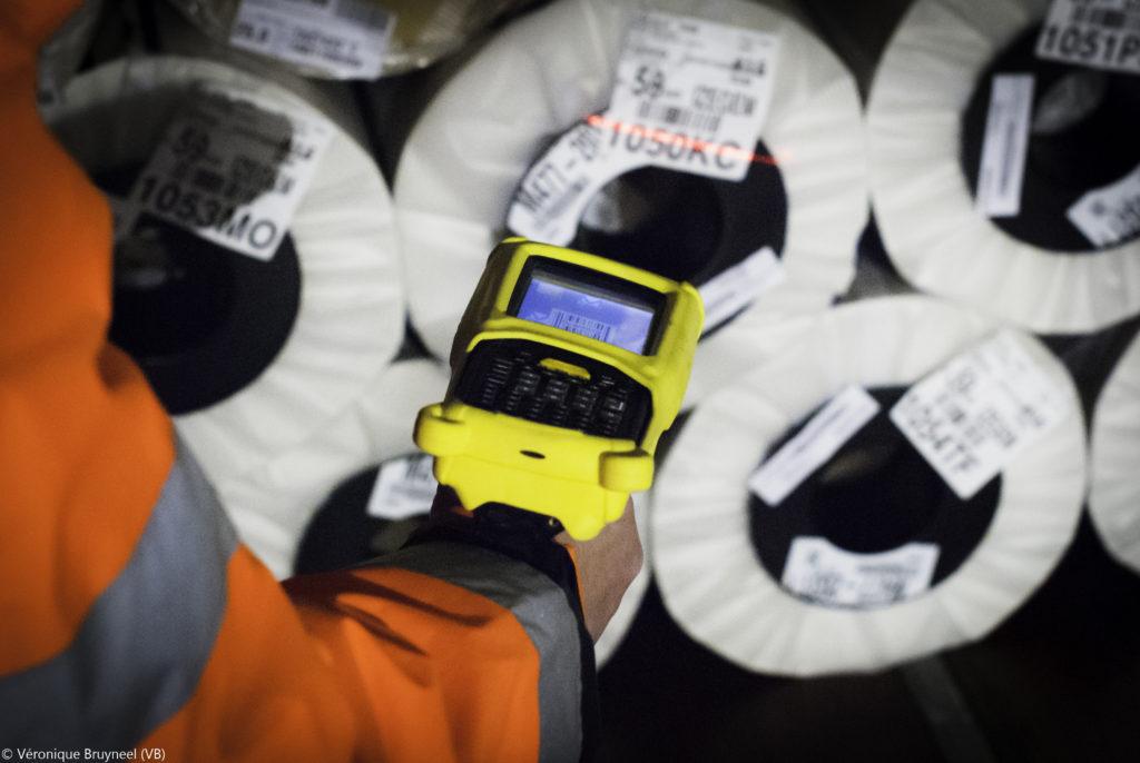Un scanner jaune en train de scanner une étiquette sur un rouleau
